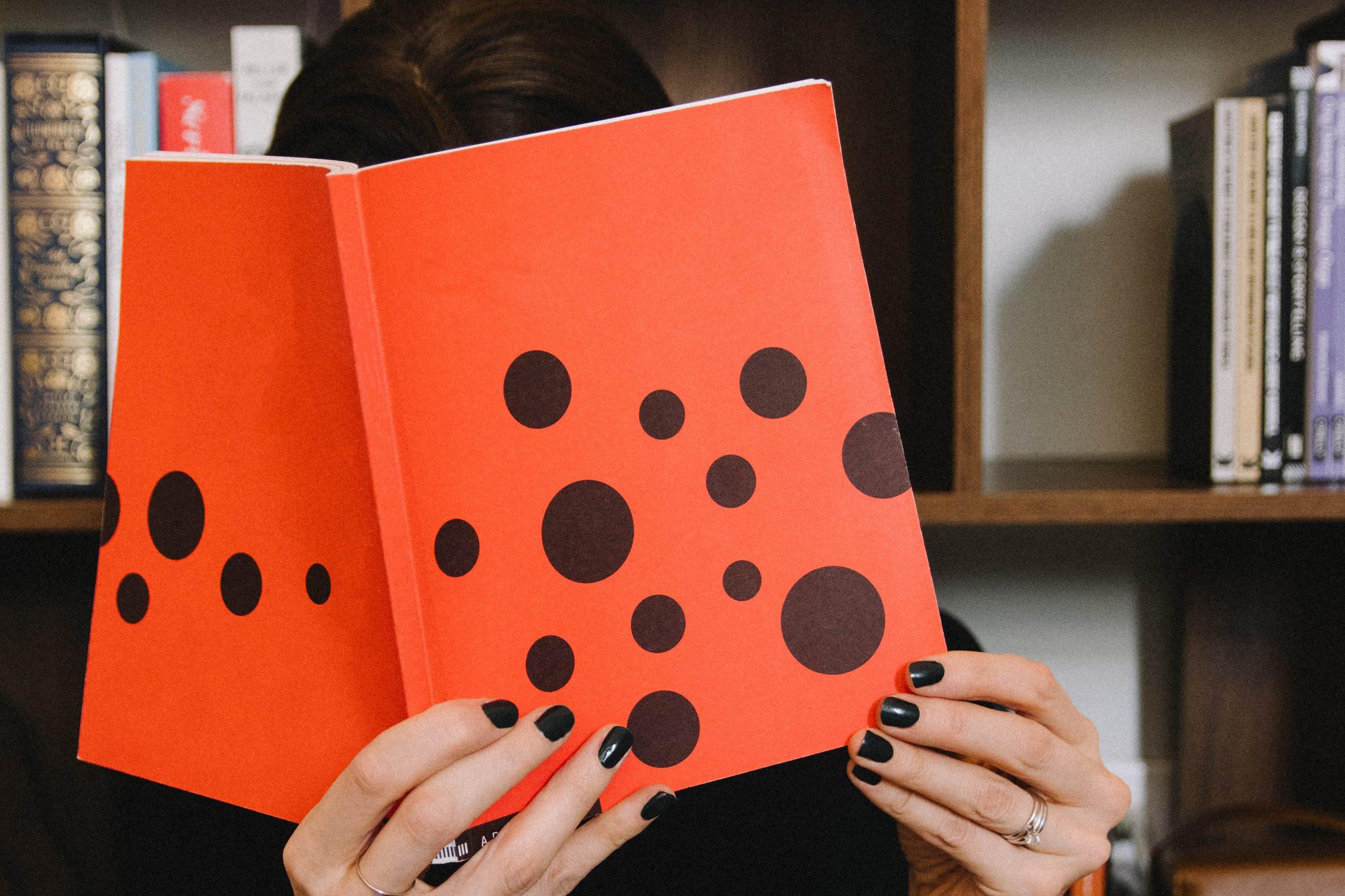 woman holding an orange book